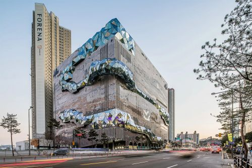 A Natural-Stone Mosaic Facade Punctuated by Dramatic Opal Windows in a New Building by OMA