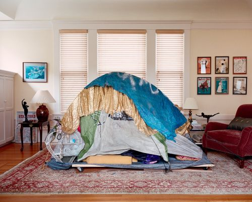 Shelters of People Experiencing Houselessness Are Photographed within Affluent Residences to Demonstrate Inequality