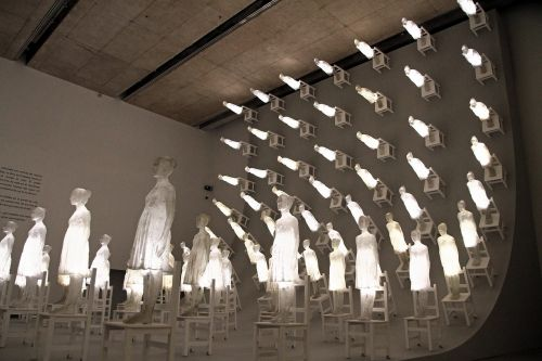 A Massive Wave of Luminous Figures Scales a Dark Wall in Ataraxia by Eugenio Cuttica
